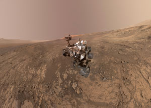 "In this photo, NASA's Curiosity rover pauses for a ""selfie"" on Vera Rubin Ridge, on the lower slopes of Mount Sharp—the peak of which can be seen directly behind Curiosity's mast. The rim of Gale Crater can be seen in the distance, on the left horizon in the image. Researchers have used data from Curiosity's navigational sensors to suggest a new explanation for the formation of Gale Crater and Mount Sharp. Image credit: NASA/JPL-Caltech (Click image to download hi-res version.)"