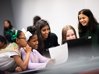 Computer science major Utsa Santhosh (center) mentors students at a Maryland Center for Women In Computing event. Her love of computing was inspired by similar events and began when Santhosh was in middle school attending a UMD summer camp for girls in computing. Image credit: Justin Derato (Click image to download hi-res version)